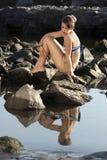 Deprimierte Frau, die auf Felsen sitzt Stockfotos