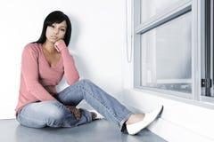 Deprimierte Frau, die auf Fußboden sitzt Stockbild
