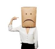 Deprimierte Frau, die auf Papiertüte zeigt Lizenzfreie Stockfotos