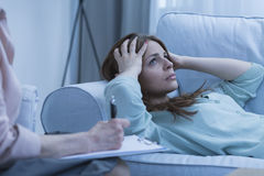Deprimierte Frau, die auf Sofa liegt Stockfoto
