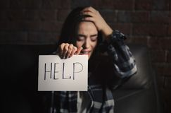 Deprimierte Frau, die Blatt Papier mit Wort HILFE hält Stockbild