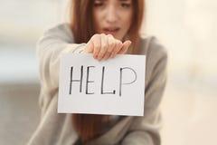 Deprimierte Frau, die Blatt Papier mit Wort HILFE hält Lizenzfreies Stockfoto