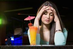 Deprimierte Frau, die Cocktailgetränk am Barzähler hat Lizenzfreie Stockfotografie
