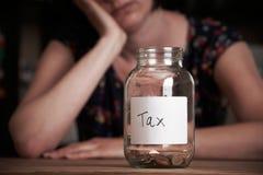 Deprimierte Frau, die das leere Glas beschriftet Steuer betrachtet Lizenzfreies Stockfoto