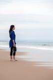Deprimierte Frau, die das Meer in einem einsamen Strand aufpasst Stockbild