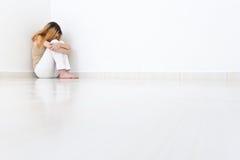 Deprimierte Frau, die in der Ecke des Raumes sitzt Die Wände sind Lizenzfreie Stockfotos
