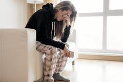 Deprimierte Frau, die in der Hand in der Couch mit Handy sitzt Stockfoto