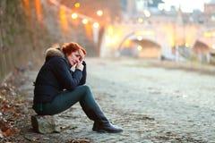 Deprimierte Frau, die in der Nähe durch das Ufer in einer Stadt eine Brücke schreit und sich fühlt einsam sitzt Stockfotografie