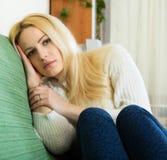 Deprimierte Frau, die in der Ruhe sitzt Lizenzfreie Stockfotografie