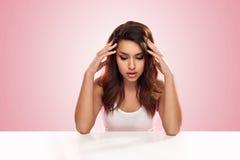Deprimierte Frau, die an einem Tisch sitzt Lizenzfreie Stockfotografie