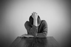 Deprimierte Frau, die an einem Tisch sitzt Stockfotografie