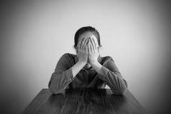 Deprimierte Frau, die an einem Tisch sitzt Lizenzfreies Stockbild