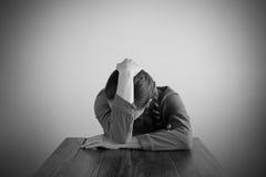 Deprimierte Frau, die an einem Tisch sitzt Stockfotos