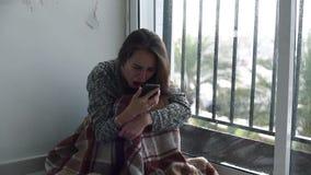 Deprimierte Frau, die am Fenster mit Regen sitzt stock video