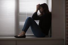 Deprimierte Frau, die am Fenster sitzt Stockbilder