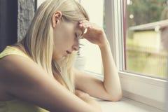 Deprimierte Frau, die am Fenster sitzt Stockfotografie