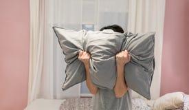 Deprimierte Frau, die ihr Gesicht mit Kissen bedeckt und in a schreit Stockfotos