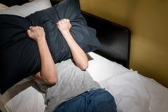 Deprimierte Frau, die ihr Gesicht mit schwarzem Kissen und screamin bedeckt Stockfoto