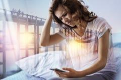 Deprimierte Frau, die ihr intelligentes Telefon hält Lizenzfreie Stockfotografie