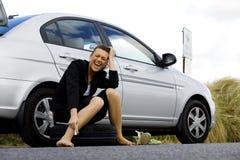 Deprimierte Frau, die an ihrem defekten Auto sitzt Lizenzfreie Stockfotografie