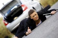 Deprimierte Frau, die an ihrem defekten Auto sitzt Stockbilder