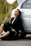 Deprimierte Frau, die an ihrem defekten Auto sitzt Stockfoto