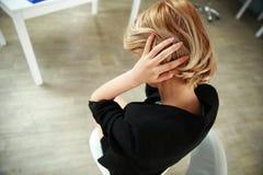 Deprimierte Frau, die im Büro sitzt Stockbild