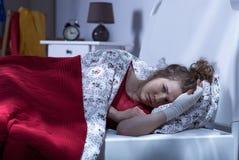 Deprimierte Frau, die im Bett liegt Stockbild