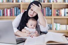 Deprimierte Frau, die mit Baby in der Bibliothek arbeitet Lizenzfreie Stockfotografie