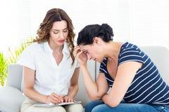 Deprimierte Frau, die mit ihrem Therapeuten spricht Lizenzfreie Stockbilder