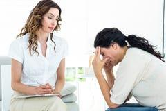 Deprimierte Frau, die mit ihrem Therapeuten spricht Stockbild