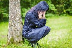 Deprimierte Frau, die nahe dem Baum im Park sitzt Stockbilder
