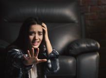 Deprimierte Frau, die nahe Ledersessel sitzt Stockfotografie