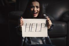 Deprimierte Frau, die nahe Lehnsessel sitzt und Blatt Papier hält Lizenzfreies Stockfoto