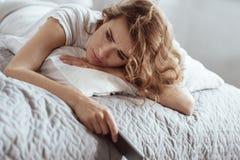 Deprimierte Frau, die negative Gedanken beim Lügen auf Bett hat Stockfotografie