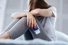 Deprimierte Frau, die Schlaftabletten hält Stockbild