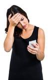 Deprimierte Frau, die Telefon hält Lizenzfreie Stockbilder