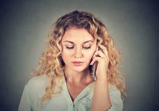 Deprimierte Frau, die am Telefon spricht Stockbild