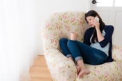 Deprimierte Frau, die vor Fenstersofa sitzt Lizenzfreies Stockfoto
