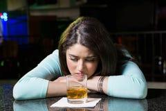 Deprimierte Frau, die Whisky am Stangenzähler isst Lizenzfreie Stockbilder