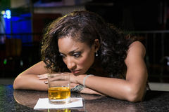 Deprimierte Frau, die Whisky am Stangenzähler isst Stockfoto