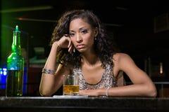 Deprimierte Frau, die Whisky am Stangenzähler isst Stockfotografie