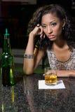 Deprimierte Frau, die Whisky am Stangenzähler isst Lizenzfreie Stockfotografie