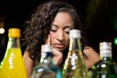 Deprimierte Frau, die am Zähler sitzt Stockfotos