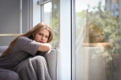 Deprimierte Frau, die zu Hause auf Sofa sitzt Stockfoto