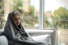 Deprimierte Frau, die zu Hause auf Sofa sitzt Lizenzfreie Stockfotografie
