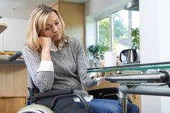Deprimierte Frau, die zu Hause im Rollstuhl sitzt Stockbilder