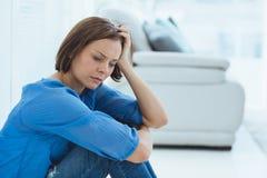 Deprimierte Frau, die zu Hause sitzt Lizenzfreie Stockfotos