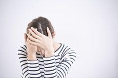 Deprimierte Frau gegen weißen Hintergrund Lizenzfreie Stockfotografie