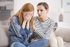 Deprimierte Frau getröstet vom Freund Lizenzfreie Stockfotos
